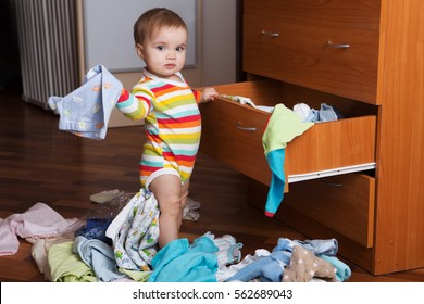 Baby throwing up clothes from wooden chest. The baby helps mother to clean the room. Little child baby playing indoors.