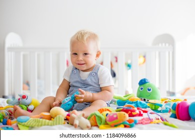 Baby toddler boy, playing in many colorful toys in sunny bedroom, smiling happily