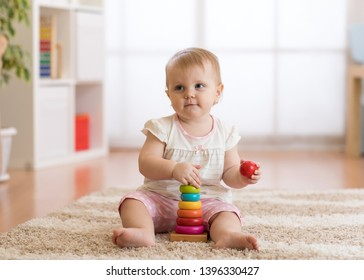Baby toddler girl having fun playing with wooden toys