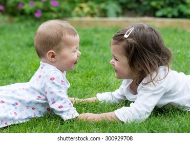 A baby and a toddler girl lying on the grass facing each other