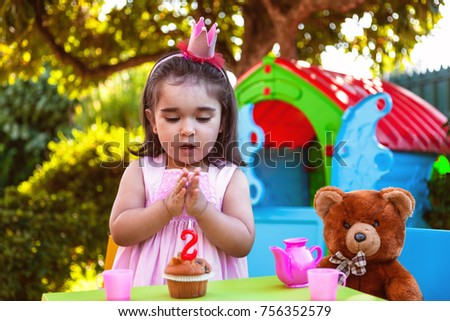 35169011fc9 Baby toddler girl in outdoor second birthday party clapping hands at cake  with Teddy Bear as
