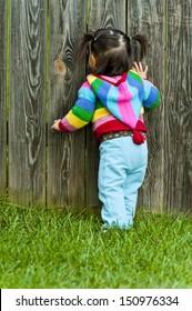 Baby toddler girl peeping through fence hole