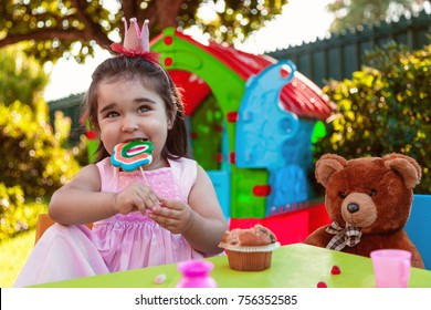 Baby toddler girl playing in outdoor tea party eating and biting a large lollipop with best friend Teddy Bear. Pink dress and queen or princess crown.