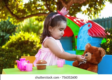 Baby toddler girl playing in outdoor tea party feeding her best friend Teddy Bear with candy gummy. Pink dress and queen or princess crown.