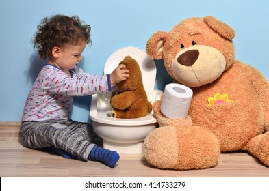 Baby toddler sitting on the floor near a potty and kissing a teddy bear. Cute kid potty training for pee and poo helped by teddy bear who gives him toilet paper