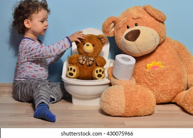 Baby toddler sitting on the potty and playing with toilet paper. Cute kid potty training for pee and poo and surrounded by teddy bears