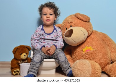 Baby toddler sitting on a potty surrounded by teddy bears. Cute kid potty training for pee and poo helped by teddy bear who gives him toilet paper