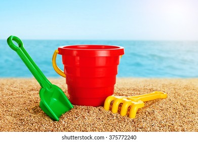 Baby toy bucket, shovel and rake in the sand. Sea background.