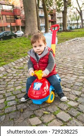 baby with a toy car in a park