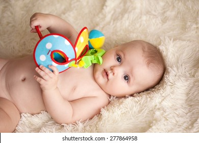 baby with toy lying on a blanket