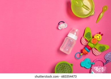 Baby toys and accessories on pink background. Top view