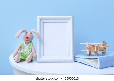 Baby toys and frame on blue wall background