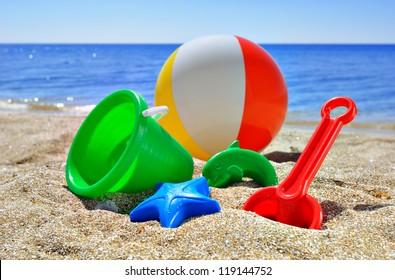 Baby toys on the beach sand against the blue sea and sky
