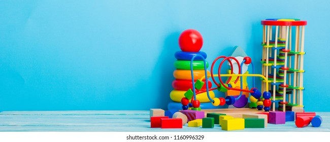 Baby toys on wooden table. Child development concept. Copy srace for text