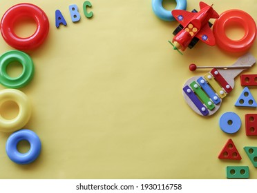 baby toys on yellow background with copy space