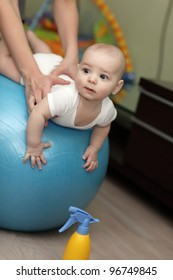 The baby training on a gymnastic ball at home