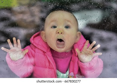 Baby trying to lick rain drops on the window's glass outside, pressing face against  the glass