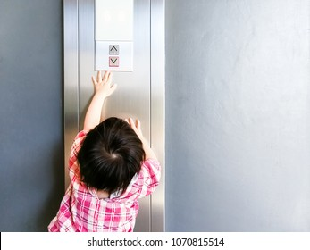 A baby is trying to pressing the elevator button up and down. A baby is stretching his arm and finger to pressing the botton.