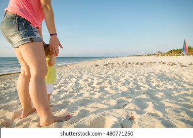 Baby trying to walk holding on to your mom. Walking on the beach