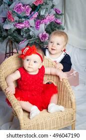 Baby twins boy and girl with gift and christmas tree