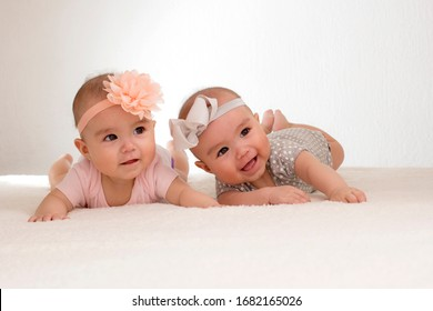 baby twins lying in bed with bow on head