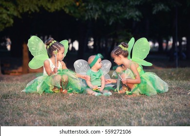 Baby and two girls in a green fairy costume with wings in the park. Kids in the park