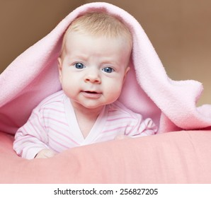 Baby under blanket. Little child at home