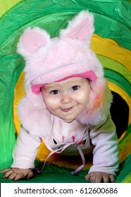 Baby using a cap with fox ears in a toy tunnel