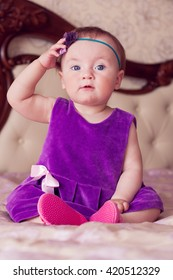 Baby in violet dress touching her headband and looking at the camera