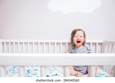 A baby wakes up in her crib crying and screaming under a cloud on the wall.