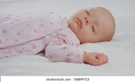 A baby waking up from sleep on a white bed at home. Medium shot.