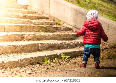 A baby walking on the street near the stairs