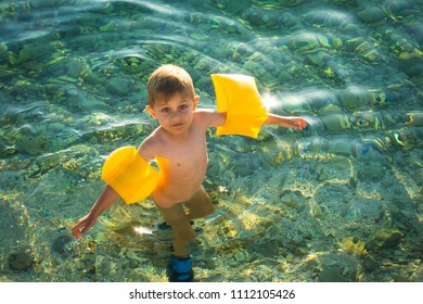 baby in water at the sea with yellow sea armrests, visible seabed of rocks