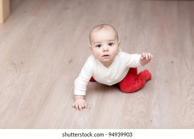 The baby waving his hand on a parquet at home