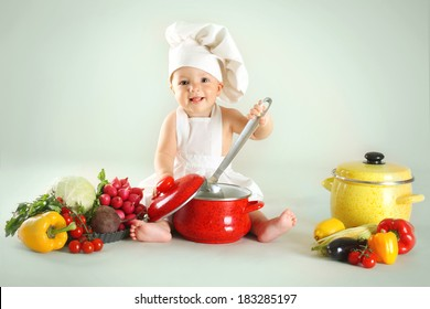 Baby wearing a chef hat with vegetables and pan. Use it for child, healthy food concept