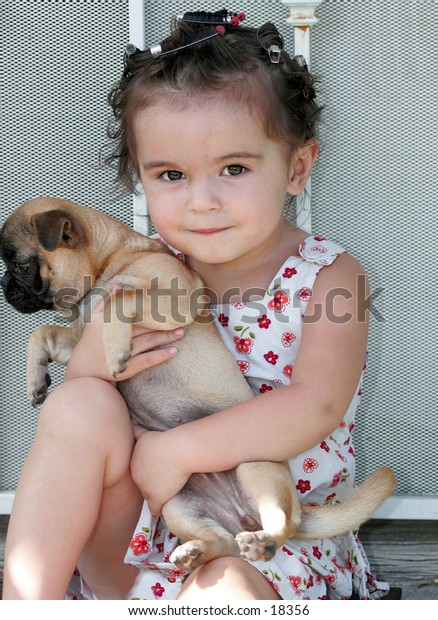 baby wearing curlers holding puppy while sitting