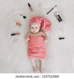 Baby wearing towel after bath. Childhood and baby care concept. Portrait of a cute funny girl 2-3 months old