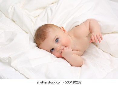 Baby in white bedding.