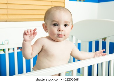 A baby in white crib Nursery interior and bedding for kid