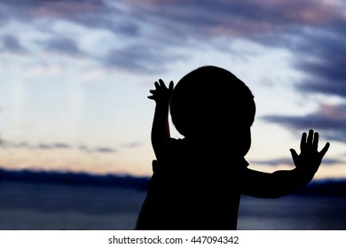 Baby at window (in partial silhouette) hands pressed against window