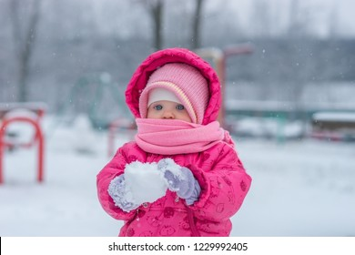 Baby in winter overalls wrapped in a scarf walks on a snow-covered street and sculpts from snow. - Shutterstock ID 1229992405