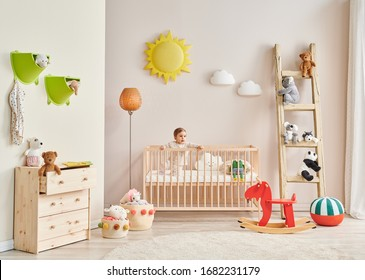 Baby in the wooden cradle and decorative modern room style.