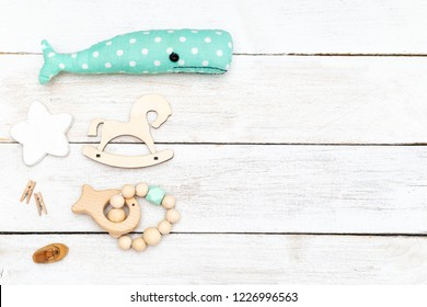 Baby wooden teether mint color and baby toys on wooden background. flat lay