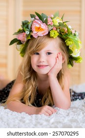 baby with a wreath on head home lies on a white carpet among the flowers