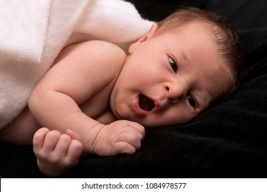 Baby yawning on black background