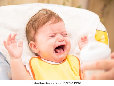 The baby in a yellow bip is crying and refusing to eat complementary foods. Child's hysterics. Closeup portrait of a crying baby on white background. Baby care and baby feeding concept