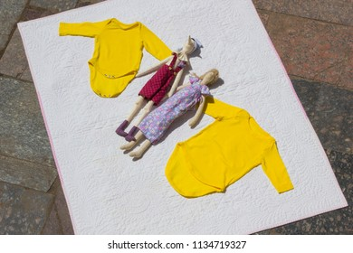 Baby yellow bodysuit, baby clothes and dolls on the white cloth, clothes for babies is a plan view a blank for designer yellow jacket small size for sale, handmade dolls for children