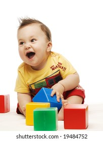 Baby in yellow shirt playing with bright colorful blocks
