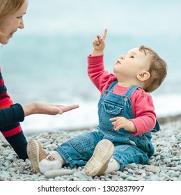 Baby and young mother playing with pebbles. Happy family is on the beach in spring. One-year-old child in denim looks up. Playful cute toddler in points his finger emotionally. Instagram style photo.