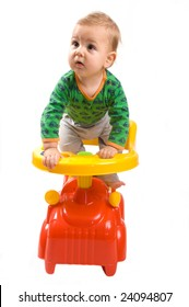Baby-boy sitting in a baby's car isolated on white background